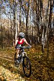 Woman mountain biking up autumn trail
