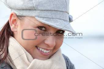 Portrait of a cute young woman with cap and scarf standing on the beach in front of the ocean