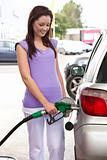Pretty caucasian woman refueling her car