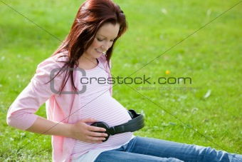 Joyful pregnant woman with headphones on her belly