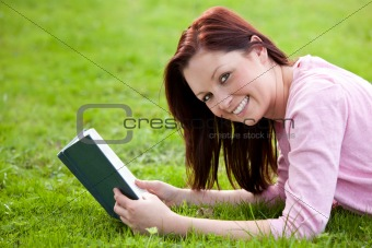 Cheerful young woman reading a book lying on the grass
