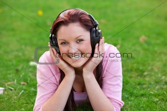 Delighted young woman listening to music with headphones lying on the grass