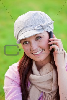 Pretty young woman wearing cap and scarf talking on phone on the grass in a park