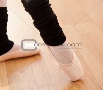 Close-up of the feet of a caucasian ballerina exercising