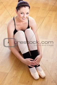 Caucasian ballerina sitting on the floor