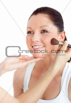Cute woman being applied powder on her face