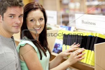 Adorable couple looking for a business book in a library