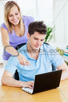 attractive woman showing something on the computer to her bf