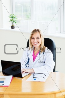 blond female doctor sitting in her office working on a laptop