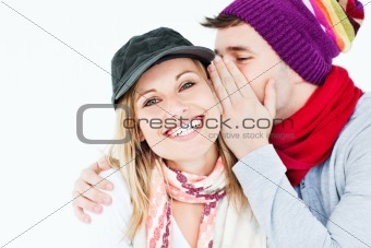 young man with cap whispering something to his female friend