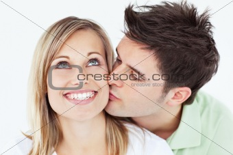 careful man kissing his smiling girlfriend against a white backg
