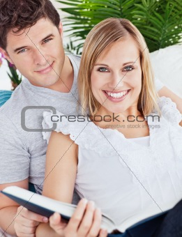 portrait of a caucasian couple reading a book sitting in the liv