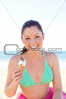 Caucasan young woman eating ice-cream on the beach