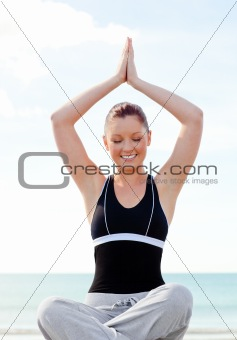 Beautiful woman practcing yoga on the beach