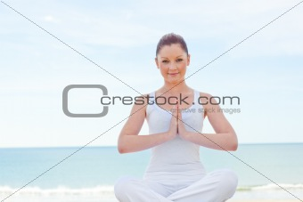 Caucasan woman practicing yoga on the beach