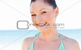 Beautiful young woman smiling at the camera on the beach