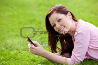 Attrative young pregnant woman lying on the grass texting