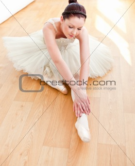 Beautiful dancer stretching on the floor
