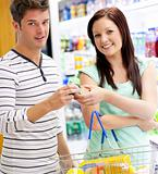 Young caucasian couple buying shampoo standing in a department o