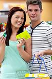 Portrait of a young couple buying cans standing in a grocery sho