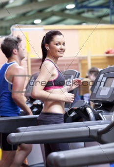 Athletic woman listening to the music while using a treadmill in