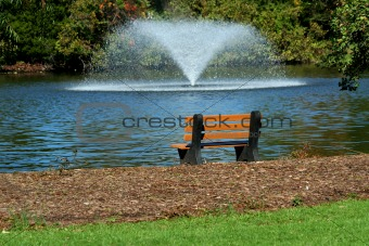 Fountain on a pond with park bench