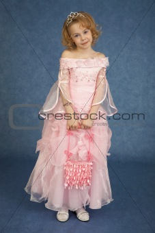 Little girl in pink dress stands on blue background