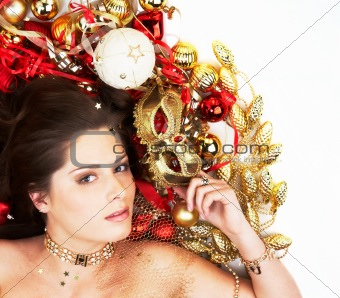 Beautiful brunette lying among Christmas decoration holding mask isolated on white