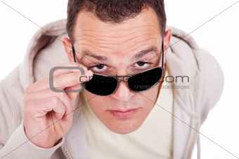 portrait of a young adult man looking over his sunglasses