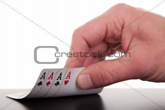 man's hand revealing four aces, isolated on white background, studio shot