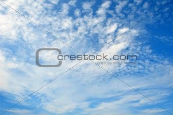 Fleecy clouds on dark blue sky