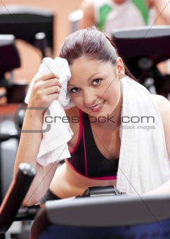Attractive woman wiping her face after exercises on a bicycle in