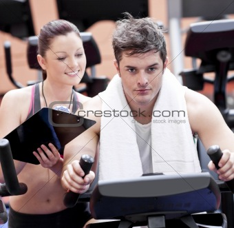 Smart female coach taking notes while her pupil is pedaling on a