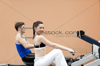 Positive woman with her boyfriend using a rower in a sport centr