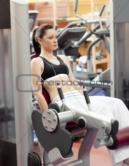 Attractive woman lifting weights with a leg press in the room of