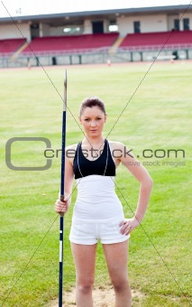 confident athletic woman ready to throw a javelin standing in a