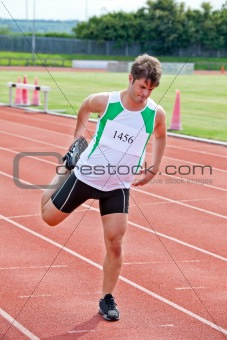 Male sprinter stretching on the starting line in a stadium