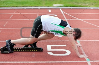 athletic man on the starting line putting his foot in the starti
