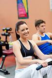 beautiful woman using a rower with her boyfriend in a fitness ce