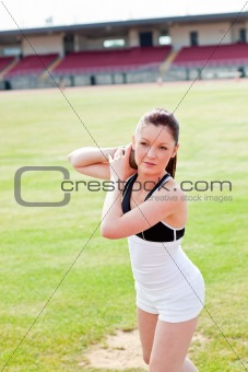 attractive athletic woman during a shot put training in a stadiu