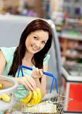 cute woman putting bananas in her shopping-basket