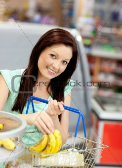 cute woman putting bananas in her shopping-basket
