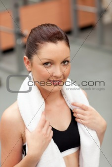 attractive athletic woman with towel around the neck smiling at