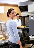 Attractive woman buying baguette in a cafeteria with baker in th
