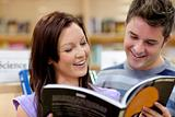 Cheerful couple reading a book in the science department of a bo