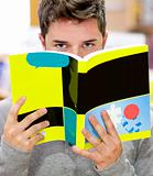 Male student standing in a book shop hiding his face behind a bo