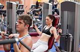 Concentrated couple using shoulder press in a fitness centre