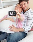 Close-up of a joyful pregnant woman and her husband taking pictu