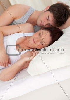adorable young future parents sleeping on the bed during the mor
