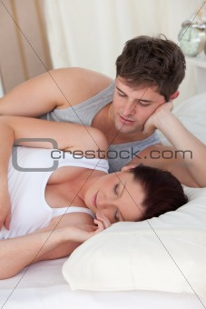 affectionate young man looking at his pregnant wife sleeping